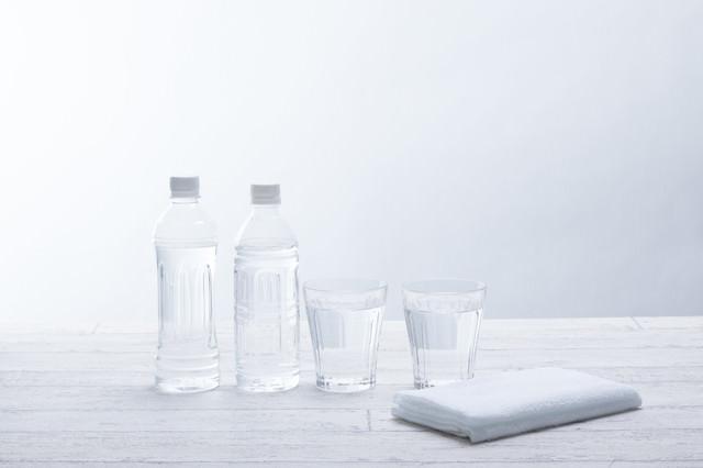 ミネラルウォーターのボトルとグラスの水の写真