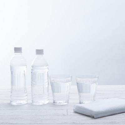 「ミネラルウォーターのボトルとグラスの水」の写真素材