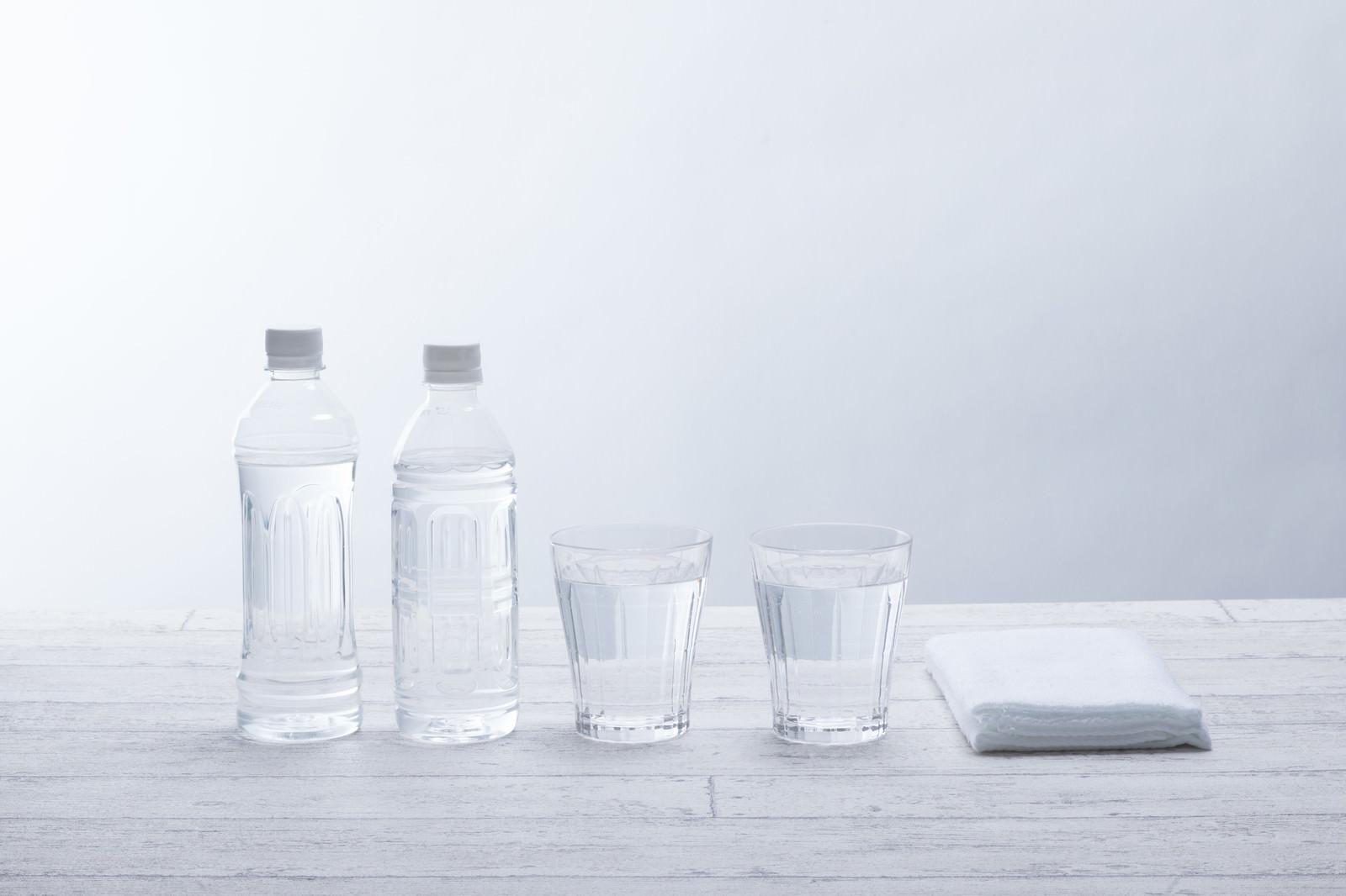 「ペットボトル2本とグラスの水」の写真