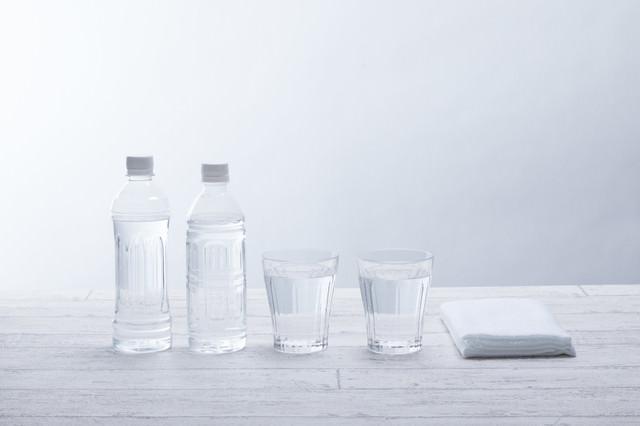 ペットボトル2本とグラスの水の写真