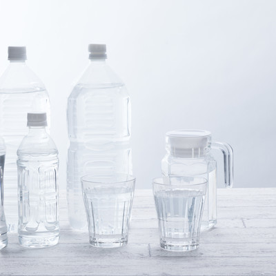 「テーブル上の飲料水(ペットボトルグラス)」の写真素材