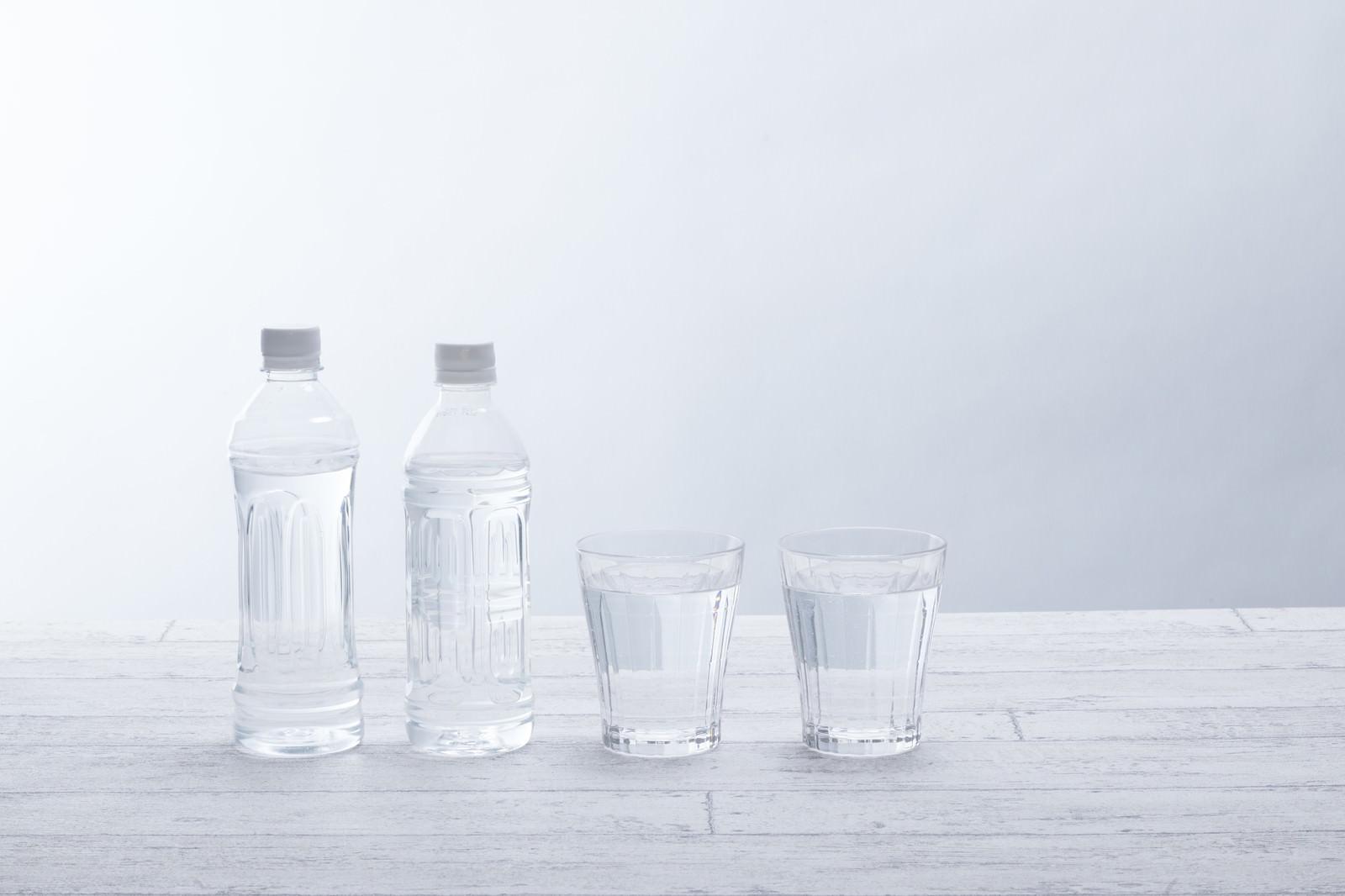 「水が入ったペットボトル2本とグラス」の写真