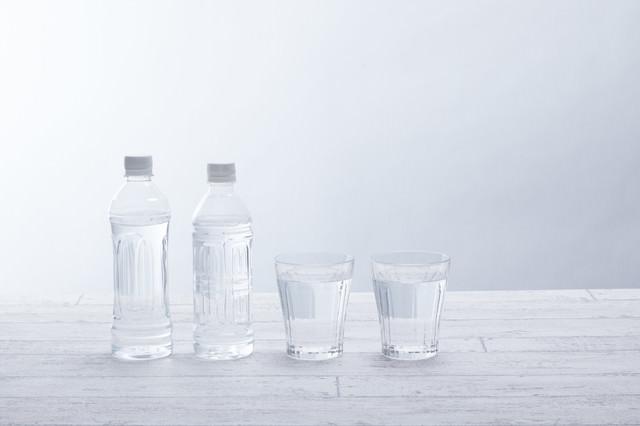 水が入ったペットボトル2本とグラスの写真