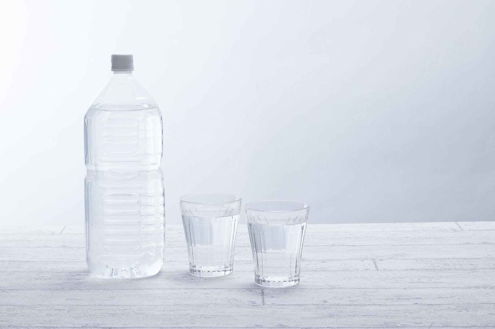 「ミネラルウォーターの2リットルペットボトルとグラス」の写真