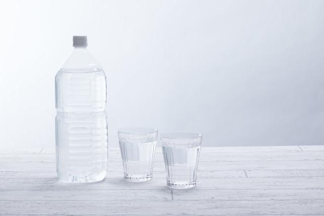 ミネラルウォーターの2リットルペットボトルとグラスの写真