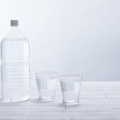 「ミネラルウォーターの2リットルペットボトルとグラス」の写真素材