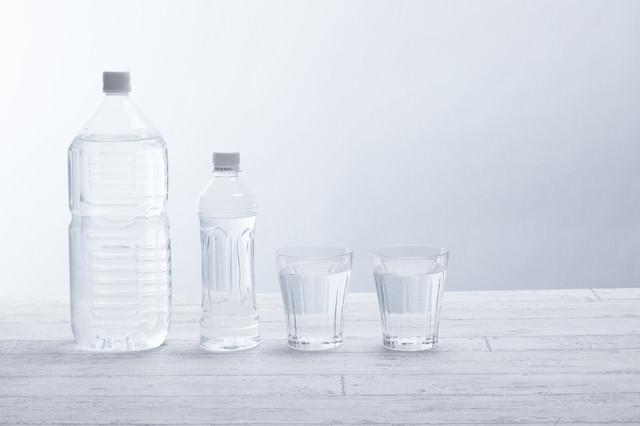 ペットボトルとグラスのミネラルウォーターの写真
