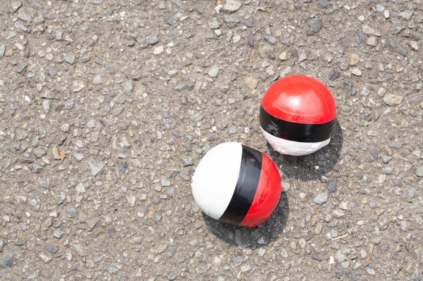 「炎天下のアスファルトと紅白ボール」の写真