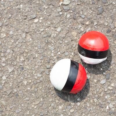 炎天下のアスファルトと紅白ボールの写真