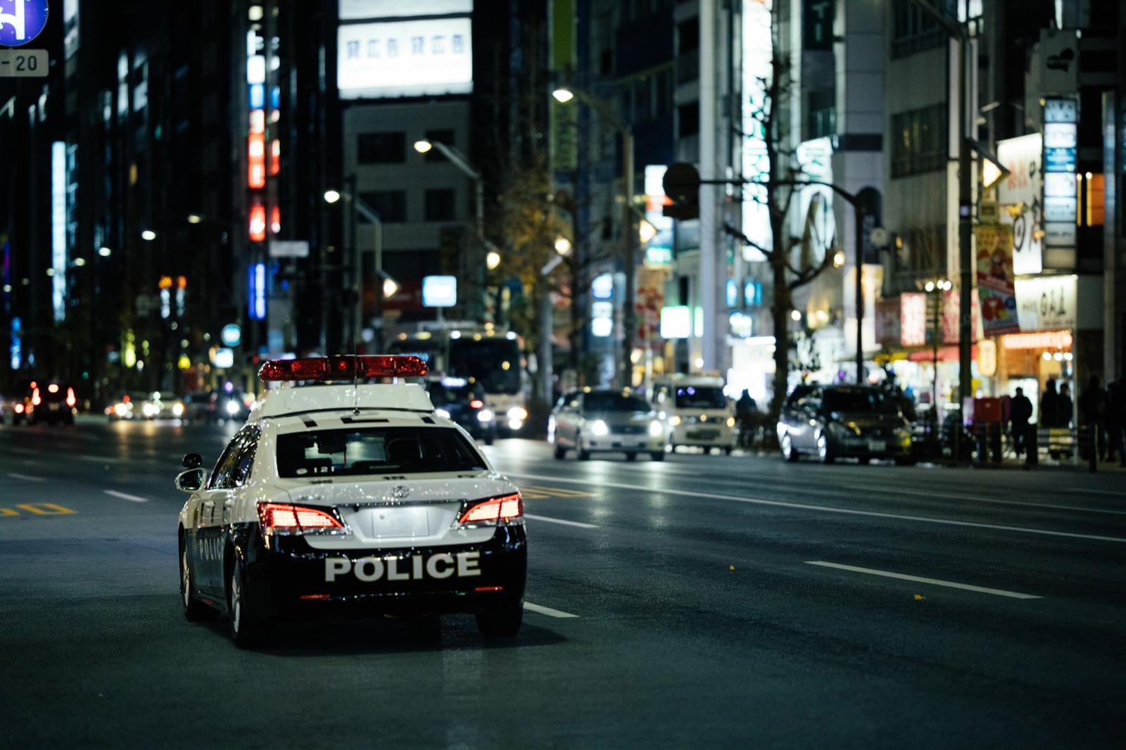 「夜の繁華街を巡回するパトカー」の写真