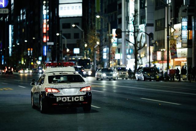 夜の繁華街を巡回するパトカーの写真