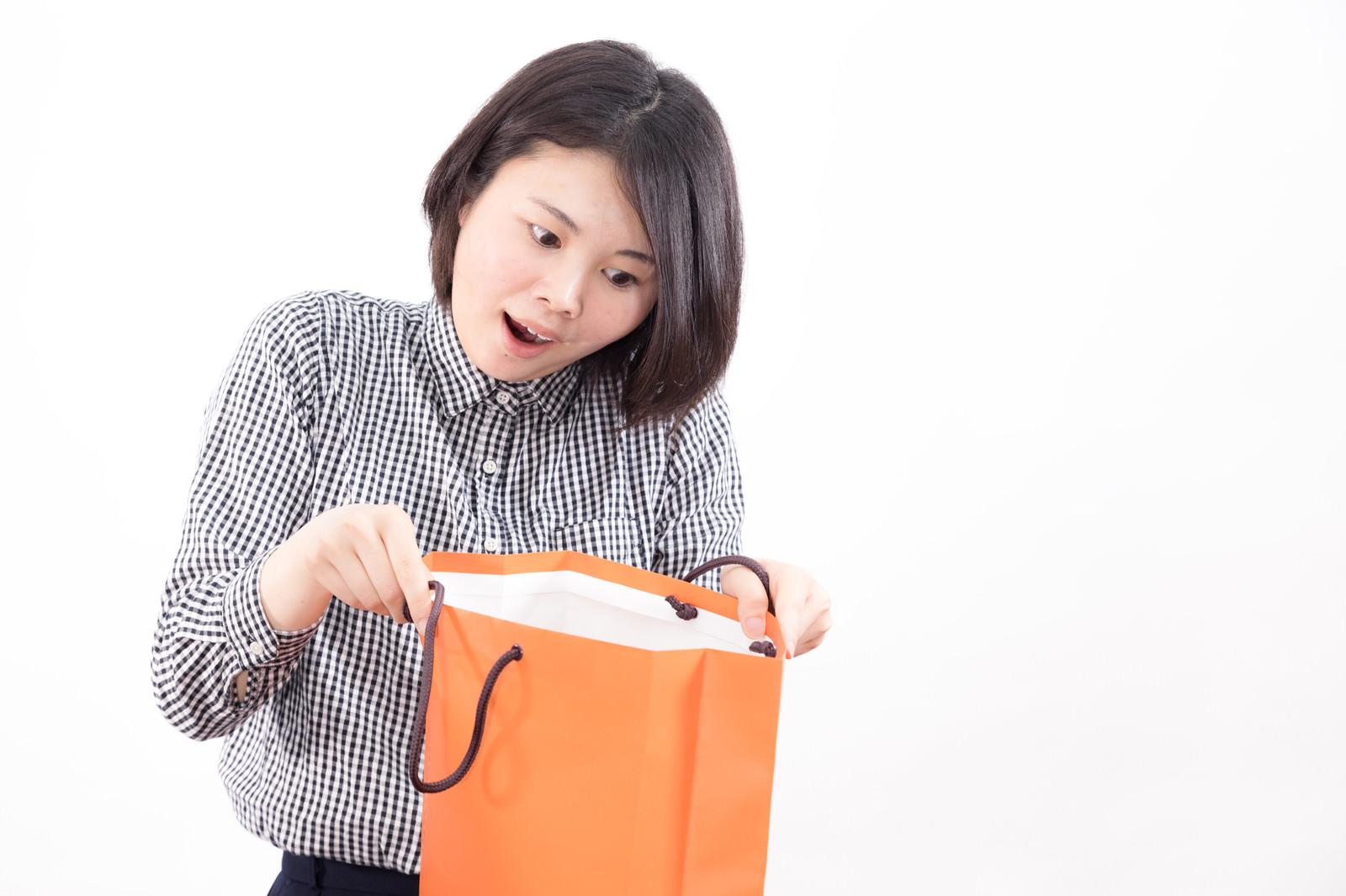 「セール品のお楽しみ袋を開封する女性」の写真[モデル:佐竹PP]