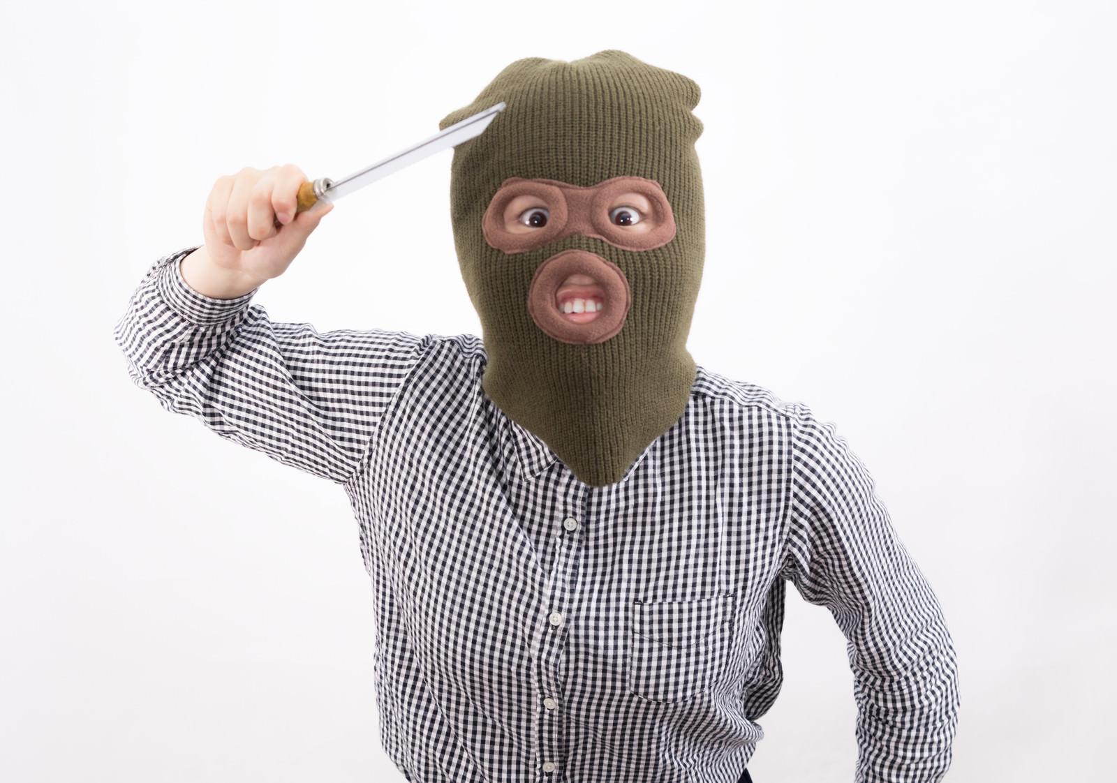 「刃物を持った覆面姿の強盗(女性)」の写真[モデル:佐竹PP]
