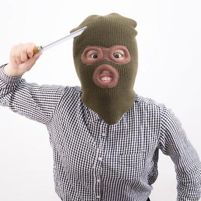 「刃物を持った覆面姿の強盗(女性)」の写真素材