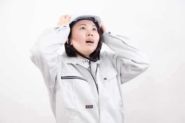 ヘルメットをおさえる女性作業員の写真