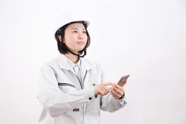 スマートフォンでリモート操作する現場作業員(女性)の写真