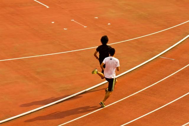競技場を走る陸上選手の写真
