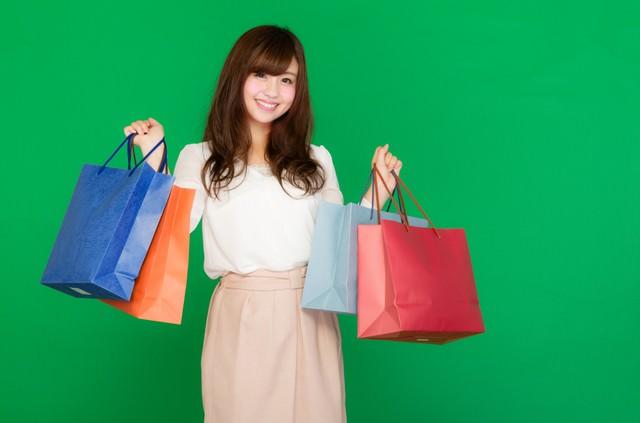 両手いっぱいの買い物袋を持ったセールが大好きな女性(グリーンバック)の写真