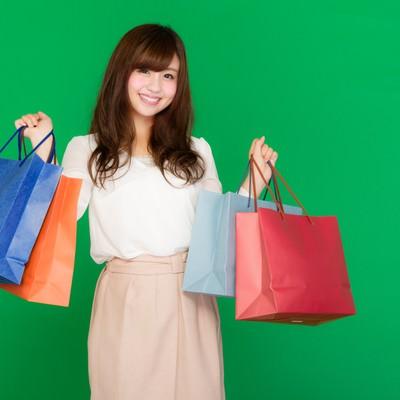 「両手いっぱいの買い物袋を持ったセールが大好きな女性(グリーンバック)」の写真素材