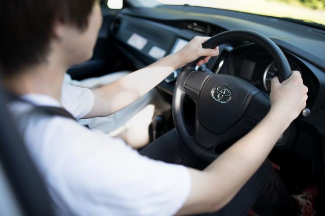 乗用車のハンドルを握る男性の写真