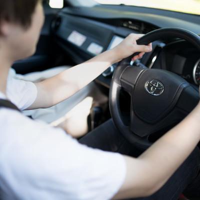 「乗用車のハンドルを握る男性」の写真素材