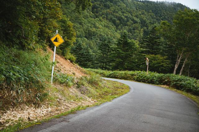 落石注意の看板と峠道の写真