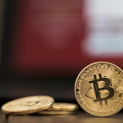 「赤い画面とビットコイン」の写真素材