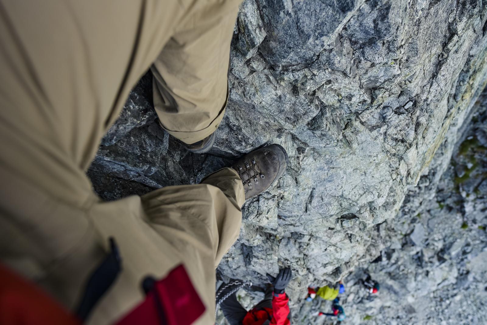「剱岳の小さな足場に足をのせる登山者の目線」の写真