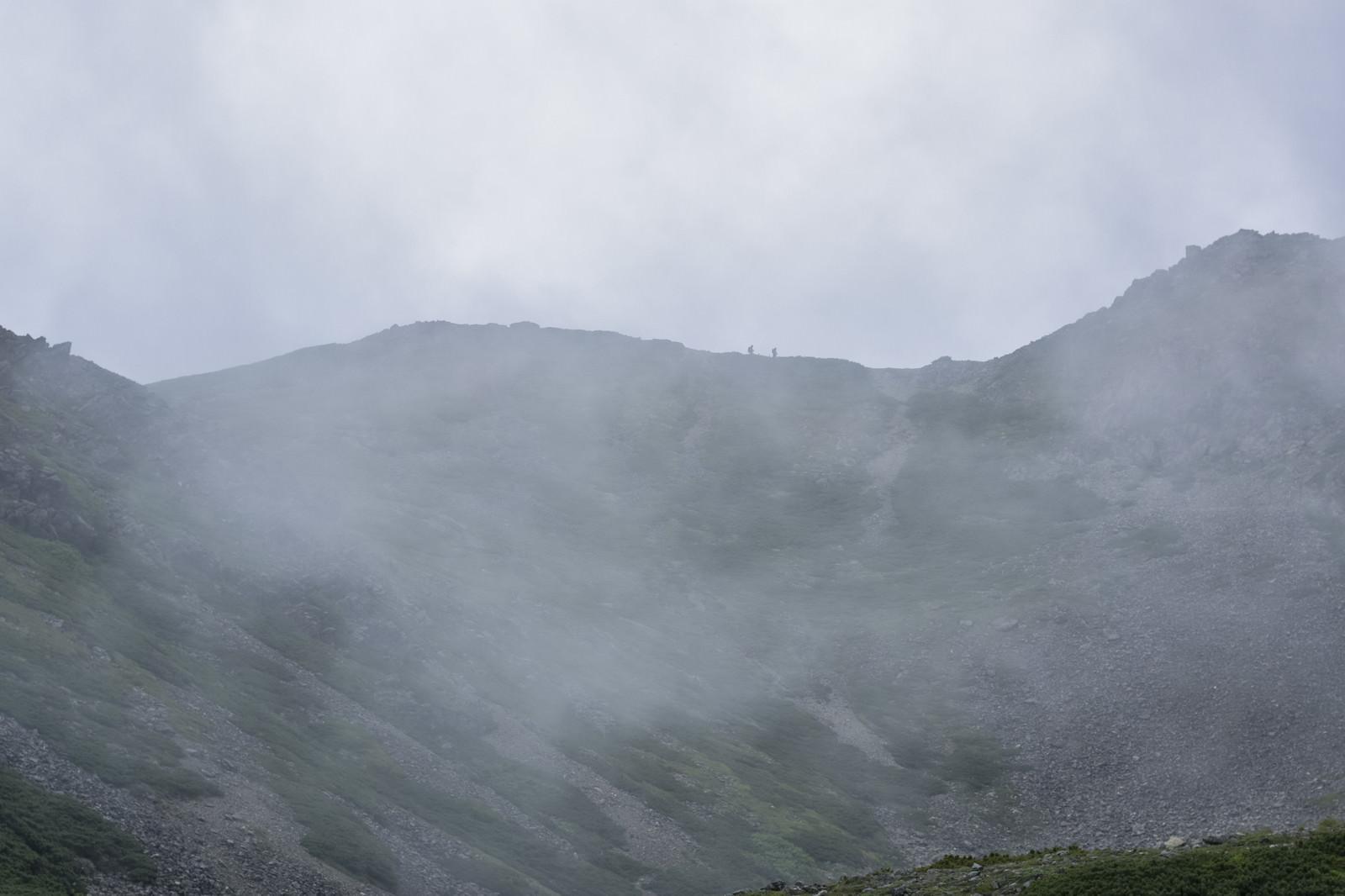 「雲に包まれる稜線を歩く登山者たち(仙丈ヶ岳)」の写真
