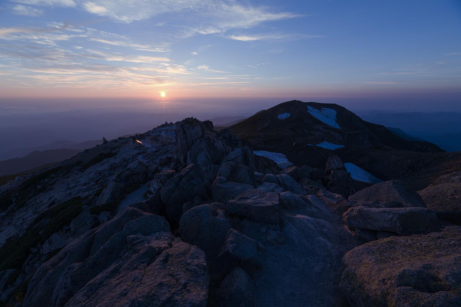 「大汝峰の向こう側に沈む往く太陽(白山)」の写真