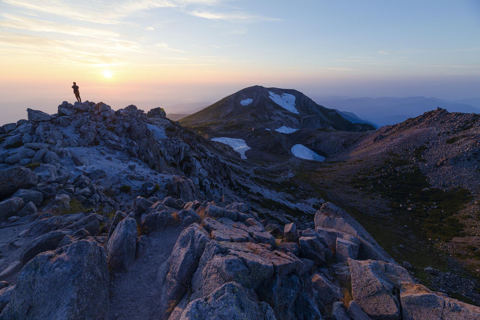 「日本海に沈む夕日を眺める御前峰の登山者(白山)」の写真