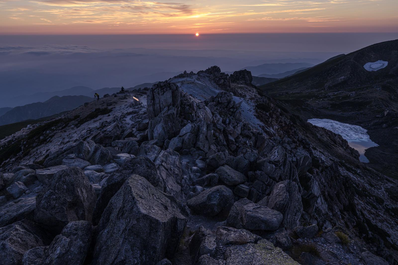 「沈みゆく太陽と白山山頂の岩」の写真