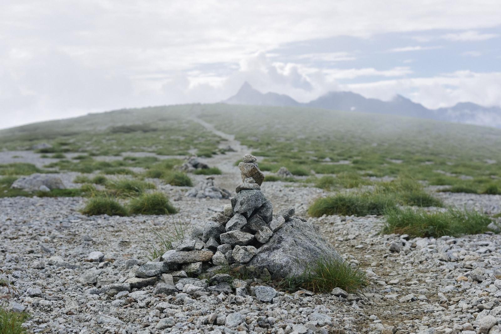 「双六岳山頂のケルンとガスの向こうの槍ヶ岳(水晶岳)」の写真