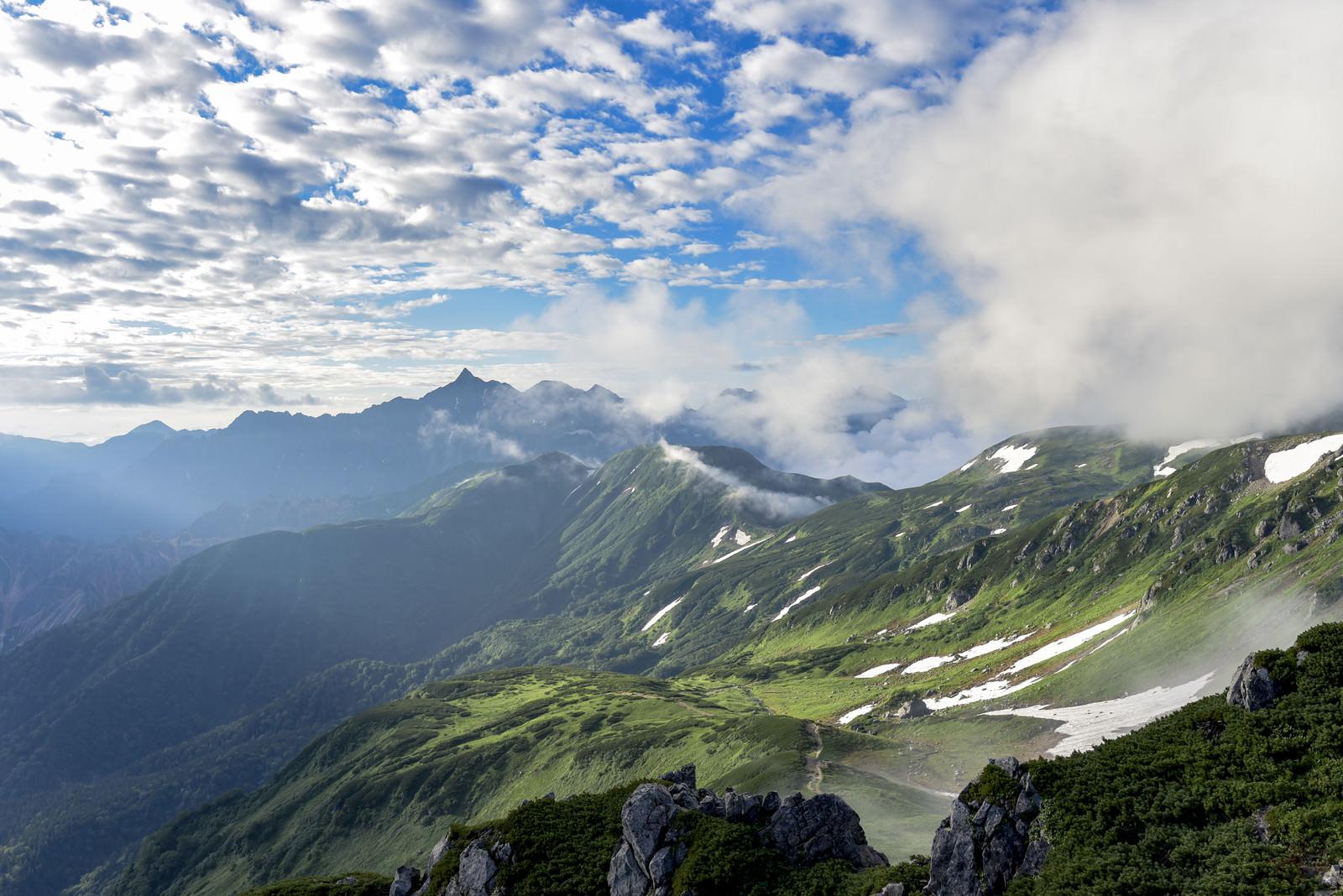 「朝日に照らされる双六山荘方面とシルエットの槍ヶ岳(水晶岳)」の写真