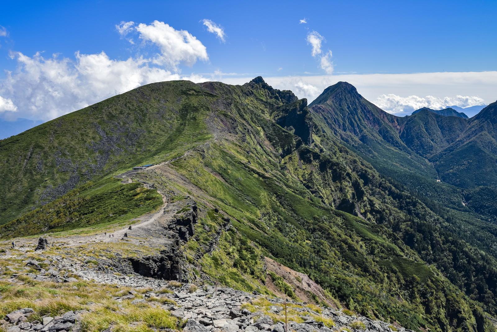 「硫黄岳の緩やかな稜線と奥に構える八ヶ岳主峰赤岳(あかだけ)」の写真