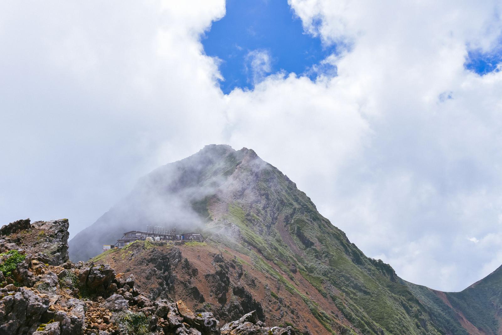 「青空の下に顔を出した赤岳山頂(地蔵尾根から)」の写真