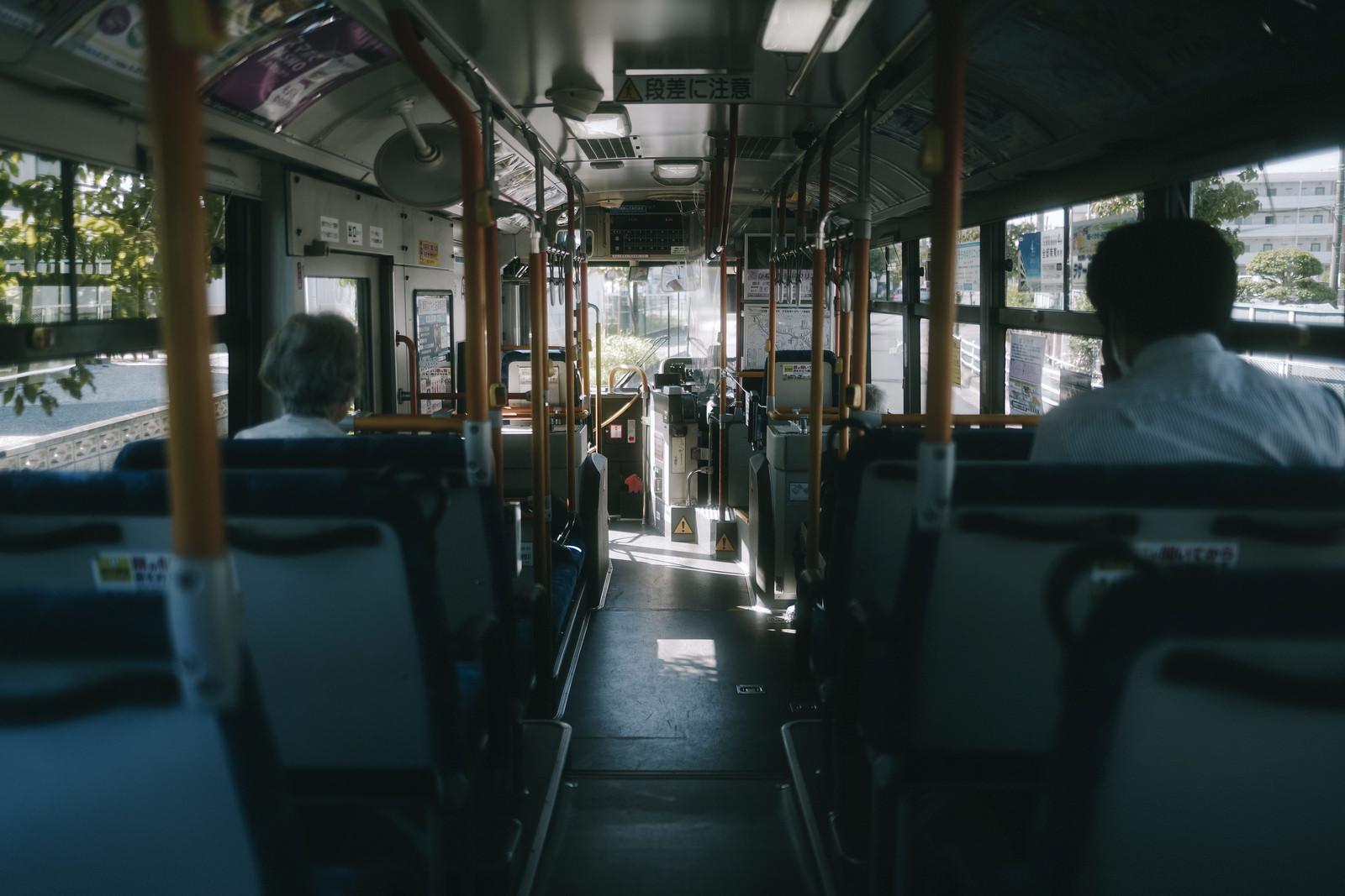 「早朝の薄暗い通勤バスの車内」の写真