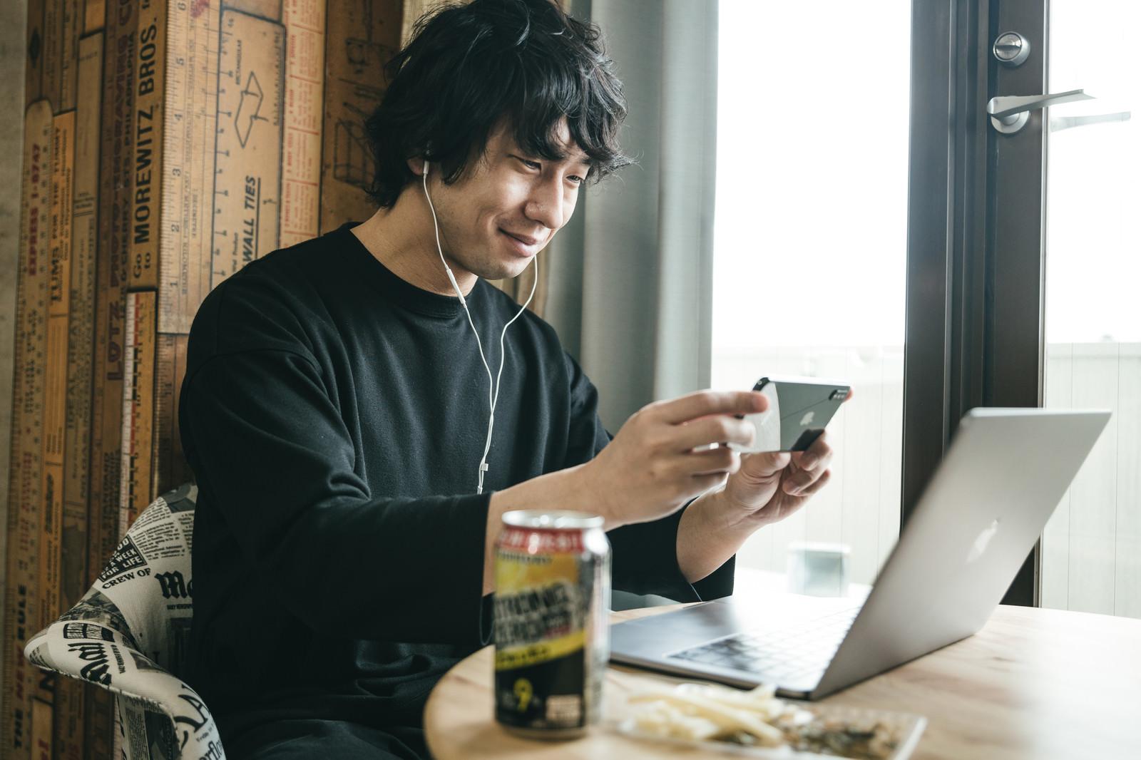 「リモート飲みの画面をスマホで撮る男性」の写真[モデル:大川竜弥]