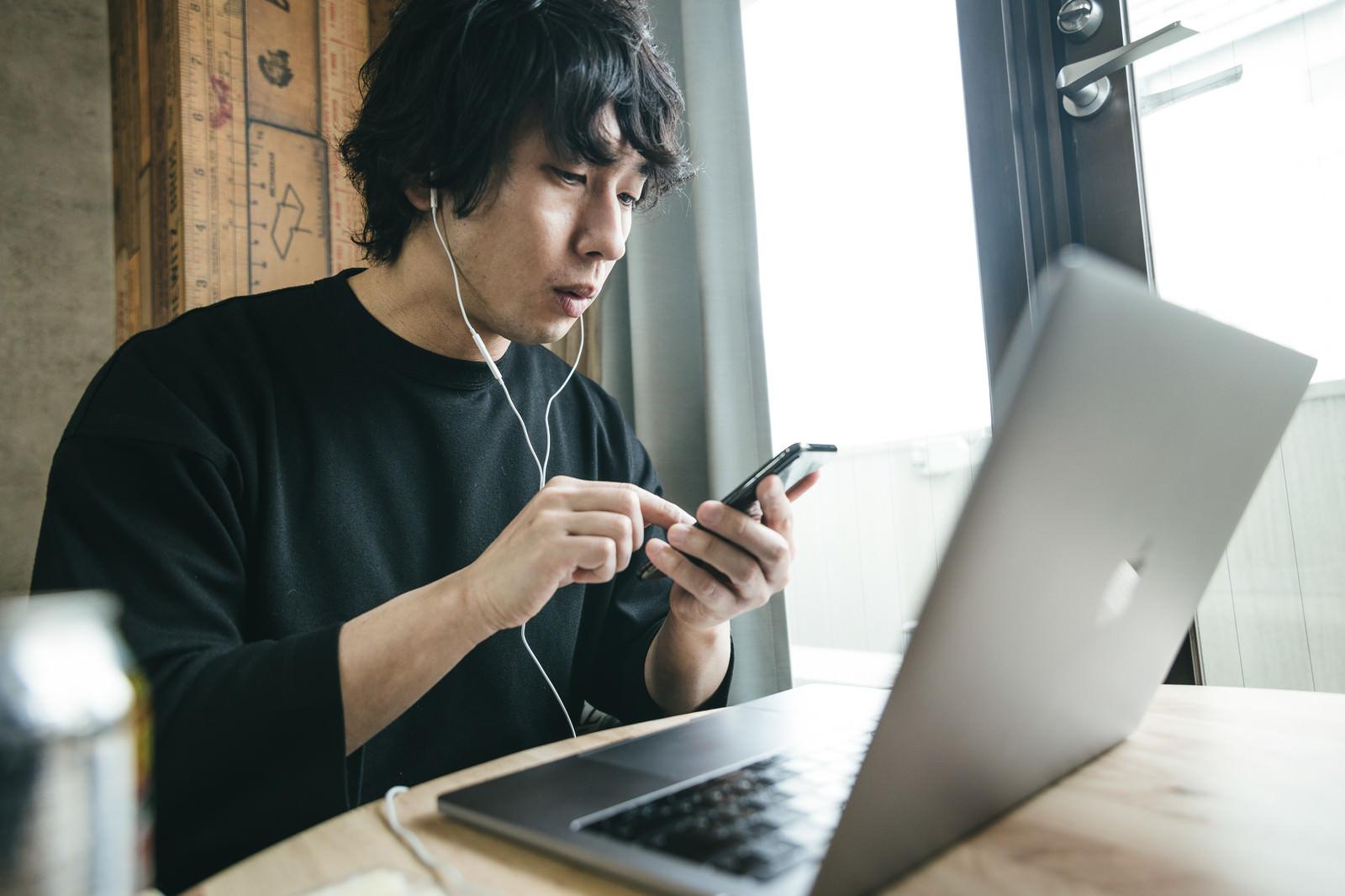 「作業中にニュースアプリをチェックするリモートワーカー」の写真[モデル:大川竜弥]