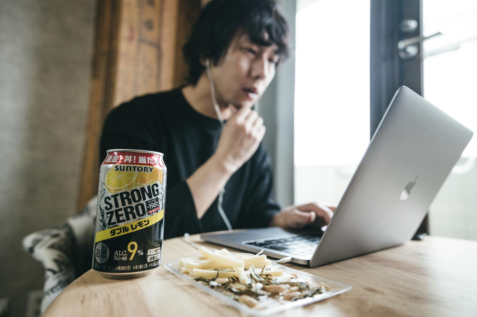 「リモートワーク中のデスクに置かれたお酒とおつまみ」の写真[モデル:大川竜弥]
