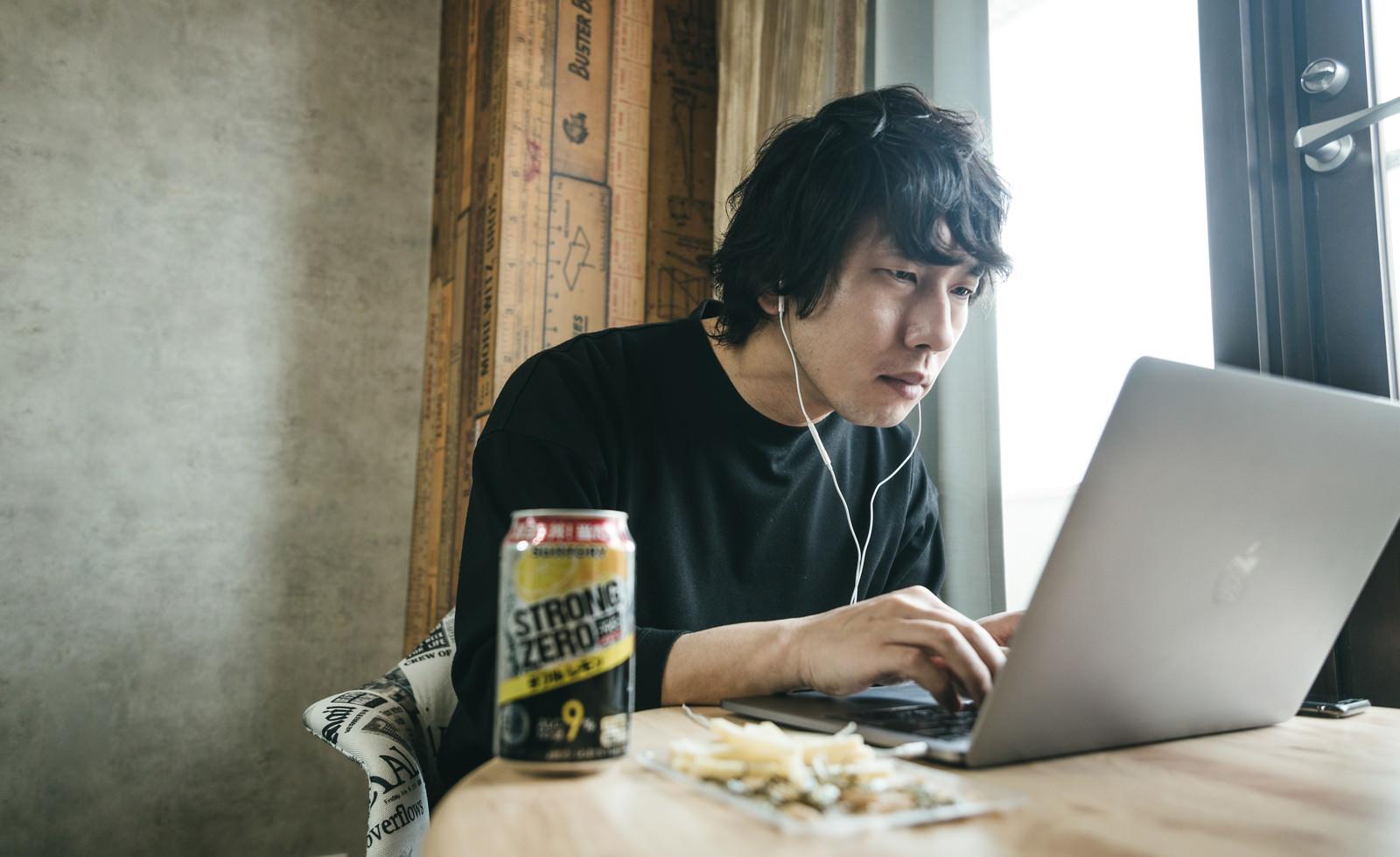 「リモート飲みでバーチャル背景機能を設定する男性」の写真[モデル:大川竜弥]