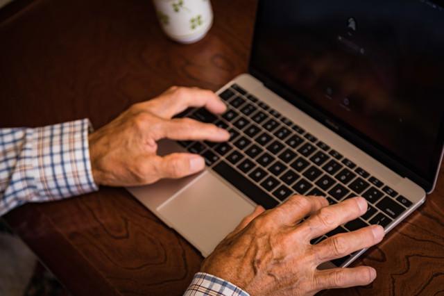 MacBookを使うおじいさんの手
