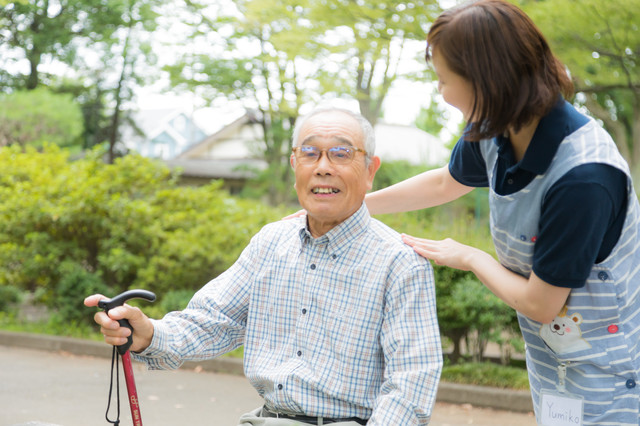 公園で日光浴を楽しむおじいさんと介護士の女性の写真