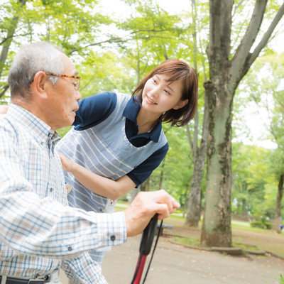 疲れた様子のお爺さんを心配する介護士の女性の写真