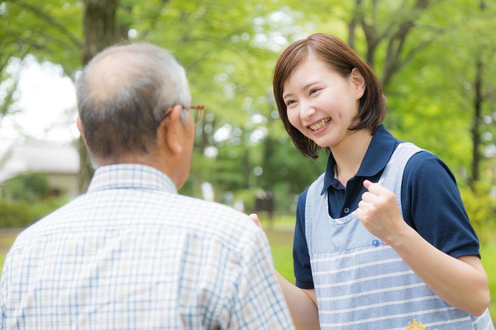 「高齢者を元気づける笑顔が素敵な女性介護士」の写真[モデル:まーちゃん yumiko]