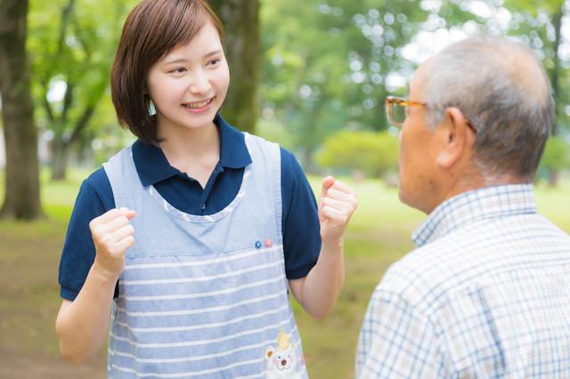 笑顔で励ます女性介護士の写真