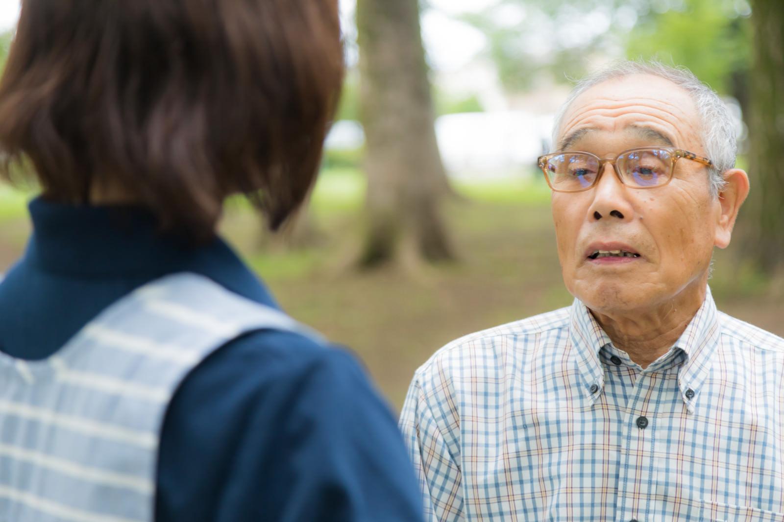 「お爺さんの話を聞く介護士」の写真[モデル:まーちゃん yumiko]