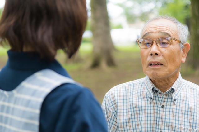 お爺さんの話を聞く介護士の写真
