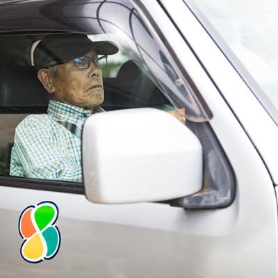 高齢者マークをつけて運転するお爺さんの写真