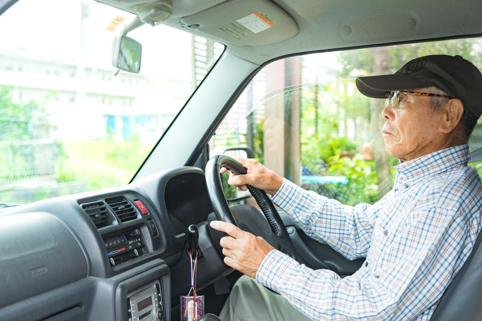 「ハンドルを握りしめる高齢者の男性」の写真[モデル:まーちゃん]